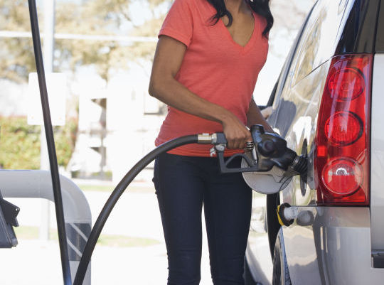 woman pumping gas - Pump prices of Petrol hits ₦160 per litre at depots in Lagos